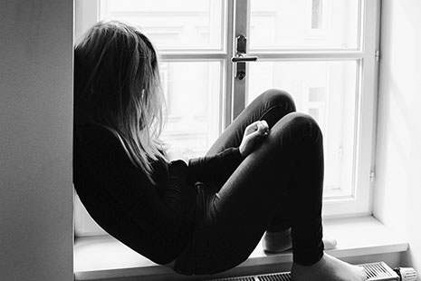 Niña sentada junto a una ventana con el pelo tapándole la cara