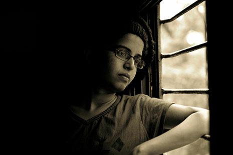 Niño con gafas cerca de una ventana con barrotes