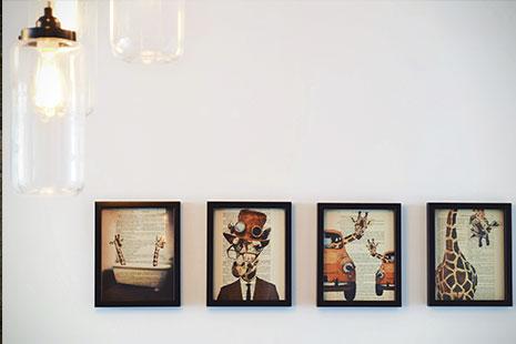Cuatro cuadros en fila bajo dos bombillas