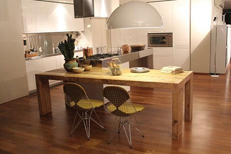 Cocina con isla de acero y madera en forma de L y lámpara blanca colgando del techo
