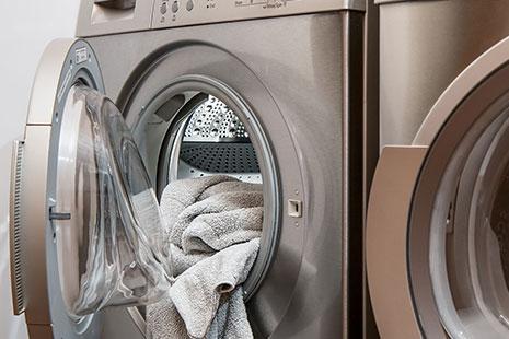 Lavadora de acero con puerta abierta y una toalla blanca dentro