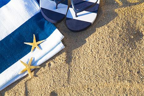 Toalla azul y blanca con sandalias azul y blancas sobre la arena de la playa