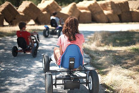 Niños de espaldas montando en kars en DiverNatura Park