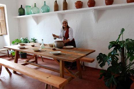 Mesa y bancos de madera y mujer vestida de payesa