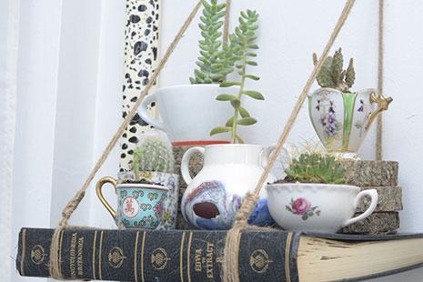 Estante hecho con un libro y macetas con pantas hechas con tazas