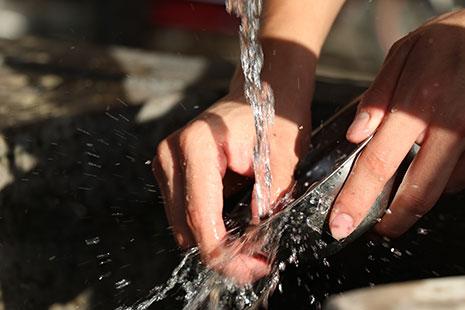 Manos sujetando un plato bajo un chorro de agua