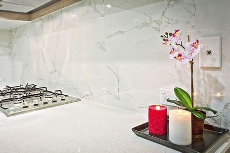Encimera de cocina blanca con velas y orquídea sobre ella