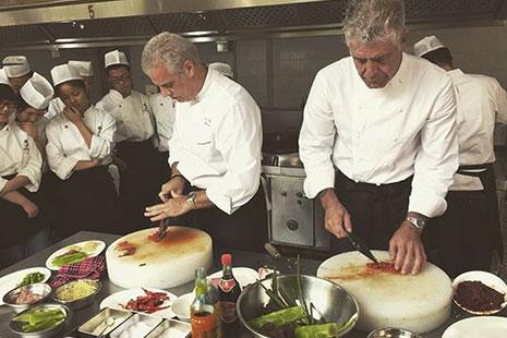 Los chefs Eric Ripert y Anthony Bourdain cocinando juntos