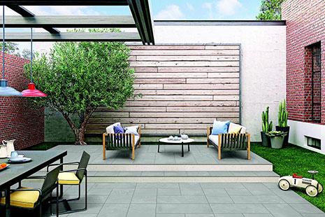Suelo gris y de hierba con meses sillas y pared de ladrillo y madera