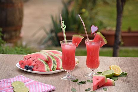 Dos copas con pajitas y contenido rojo junto a trozos de sandía