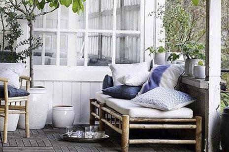 Muebles de madera con textiles blancos y morados en una terraza