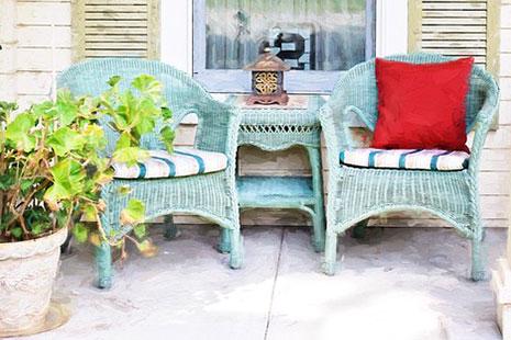 Sillas y mesa de mimbre azul, cojín rojo y planta en un porche
