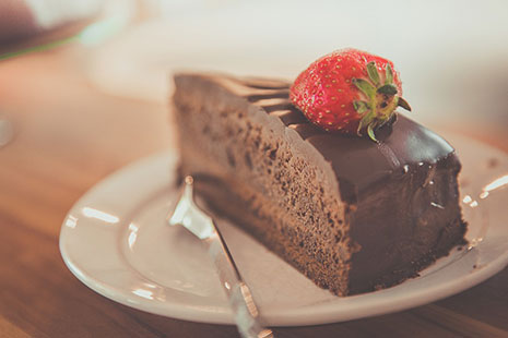 Porción de tarta de chocolate con fresa encima, y tenedor