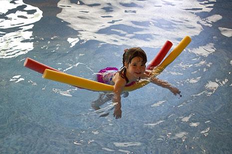 Niña en el agua con bañador y dos churros de natación bajo los brazos