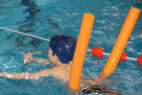 Niño en el agua con gorro de baño azul y churro de natación bajo la cintura