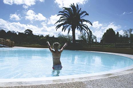 Persona dentro de piscina redonda con el agua por las nalgas y brazos en alto