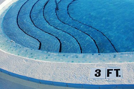 Diferentes escalones con barandilla dentro de una piscina