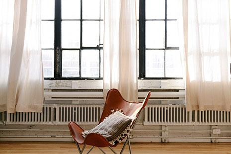 Silla de cuero con cojín y ventanales con cortinas blancas