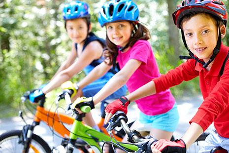 Niña con camiseta rosa y casco azul sobre bicicleta entre otros dos niños con casco y bici