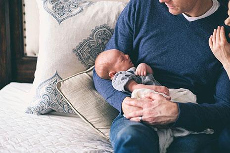 Hombre con bebé en brazos sentado en la cama