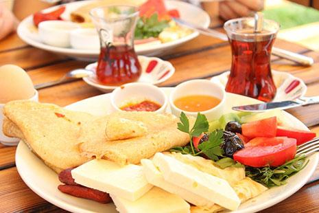 Plato con diferentes alimentos, tazas de té y huevo cocido