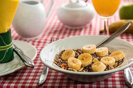 Plato con cereales y rodajas de plátano, copa con zumo, tazas y cubiertos sobre mantel de cuadros