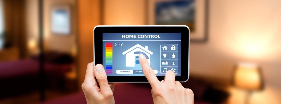 dos manos sostienen una tablet en la que se muestra el dibujo de una casa y controles de temperatura