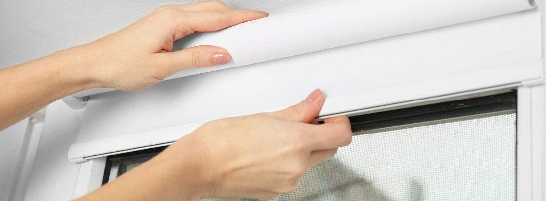 manos de mujer colocan un estor blanco sobre una ventana