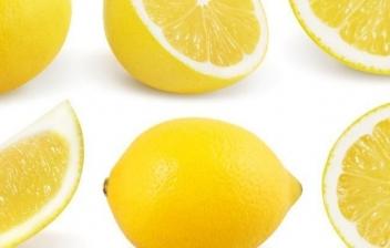 Limones y hojas verdes sobre madera blanca