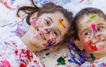 Un niño lleno riéndose lleno de pintura