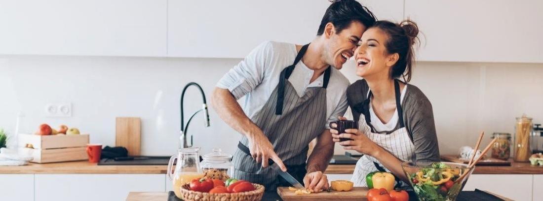 Una mujer y un hombre se sonríen mientras preparan unas pizzas