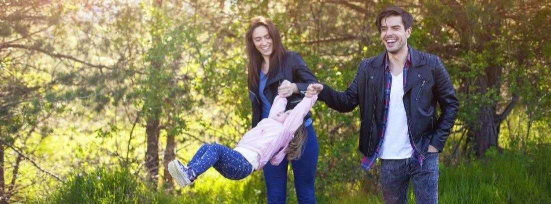 Padre y madre cogiendo a un niño por los brazos en una tarde soleada en un parque