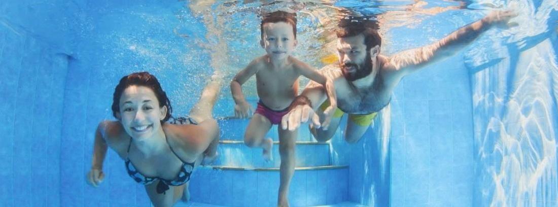 Padre practicando natación con sus dos hijos