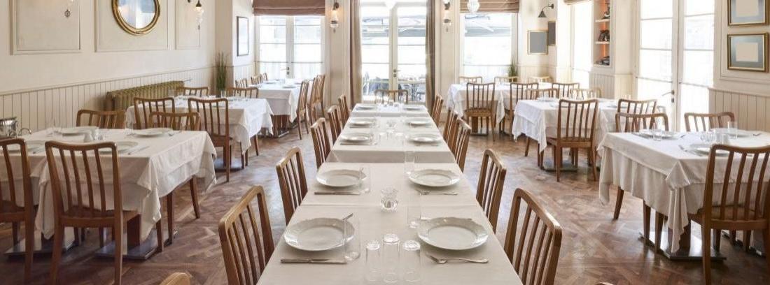 Mesa larga de madera con sillas blancas