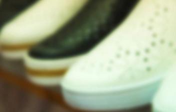 Una chica con cara de sorpresa sentada en el suelo y rodeada de zapatos