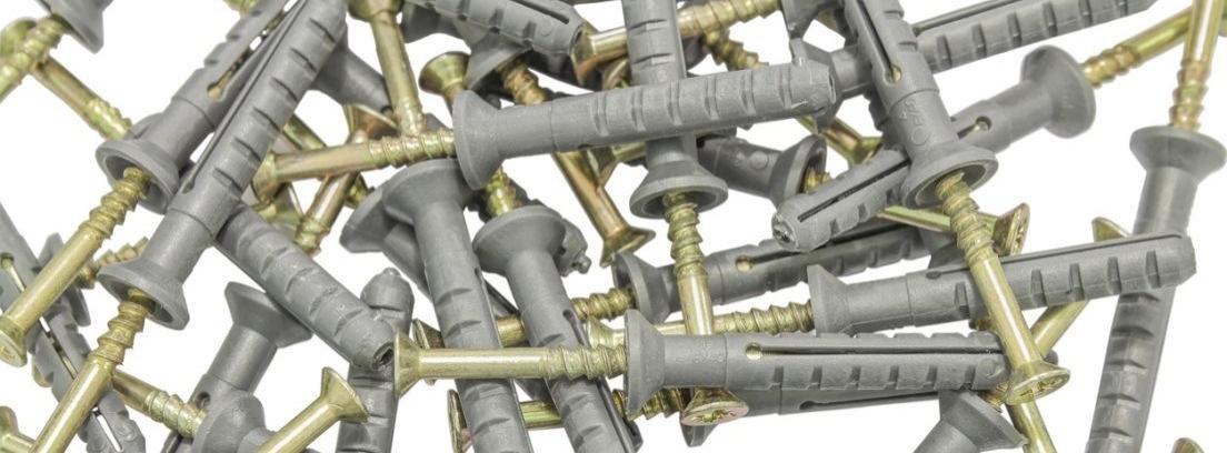 Varios tacos de plástico gris con sus tornillos