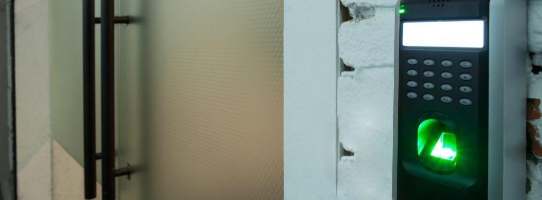 Una mano pulsa las teclas de una cerradura electrónica de una puerta blanca y de cristal
