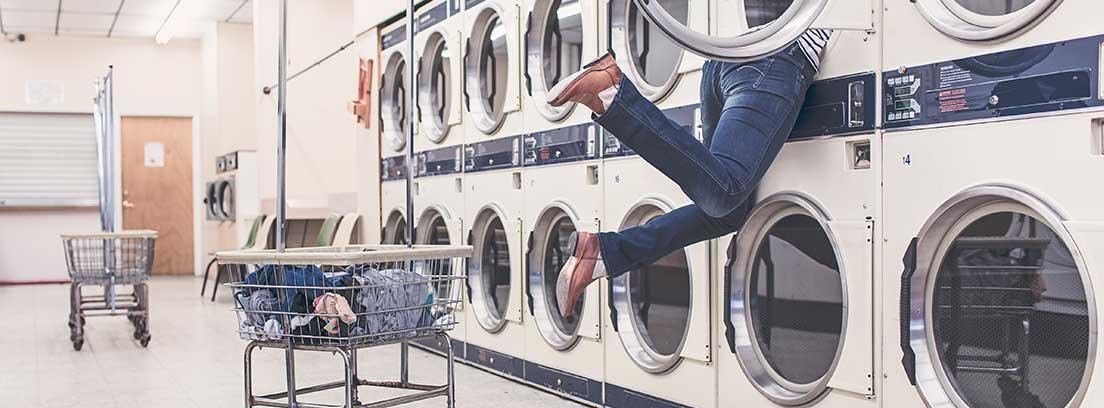 Mujer con medio cuerpo metido dentro de una lavadora en una lavandería