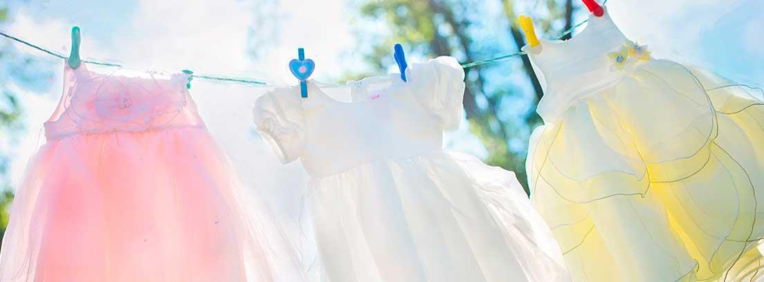 Tres vestidos de niña colgados con pinzas en una cuerda de tender la ropa
