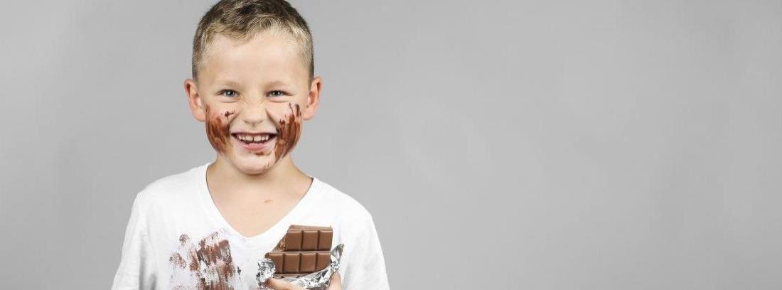 Niño manchado la ropa y la cara de chocolate