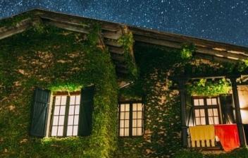 Fachada con ventanas con contraventanas de madera de color azul y flores.