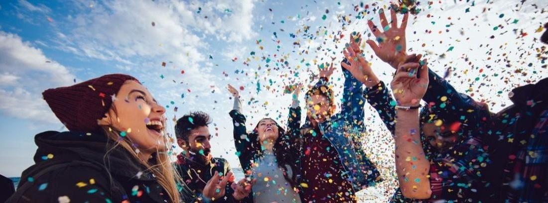 Seis jóvenes con semblante festivo levantan los brazos bajo una nube de confeti