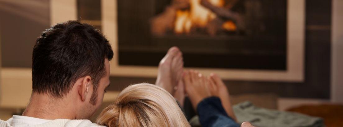 Hombre y mujer abrazados y sentados en un sillón frente a una chimenea encendida