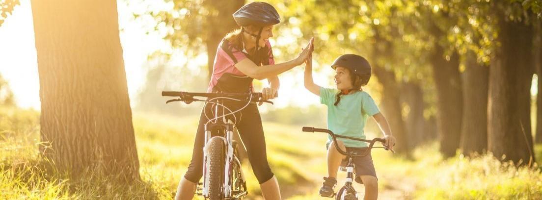 Padre enseñando a montar bici a su hija