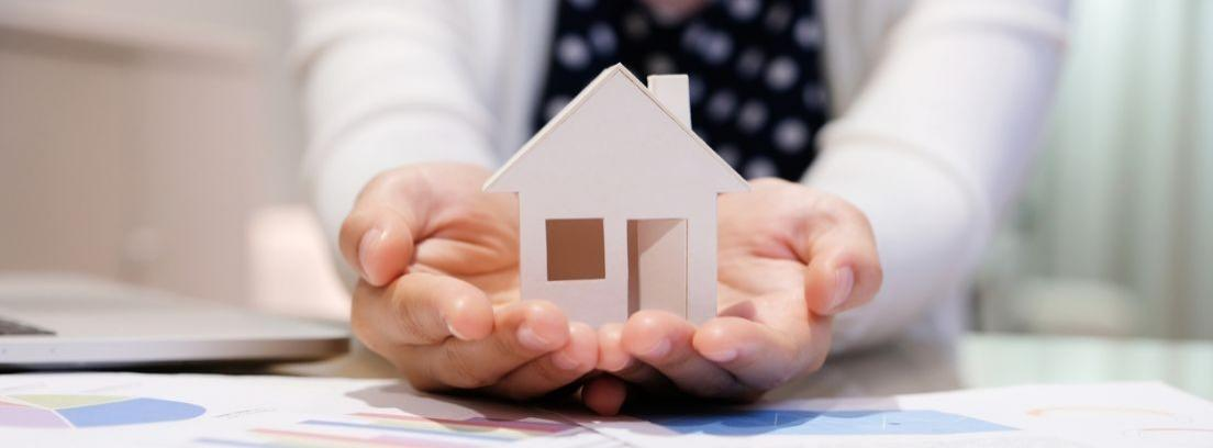 Maqueta de una casa sujetada por dos manos