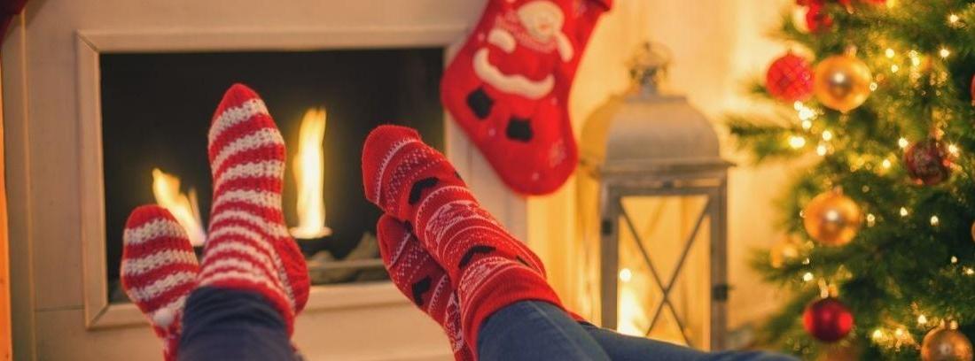 Cuatro calcetines navideños colgados de la repisa de la chimenea