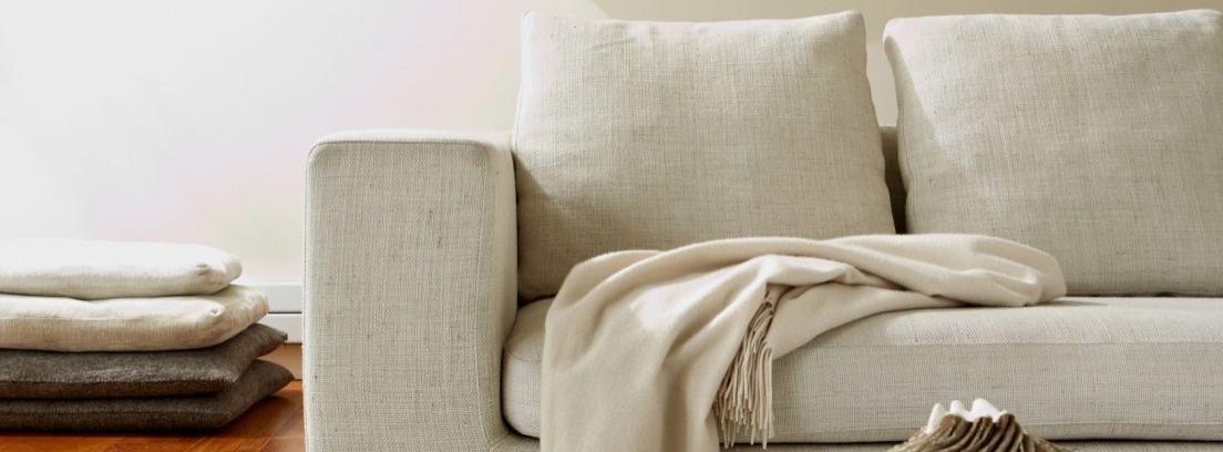 Sofá de tela blanco en salón blanco y color madera
