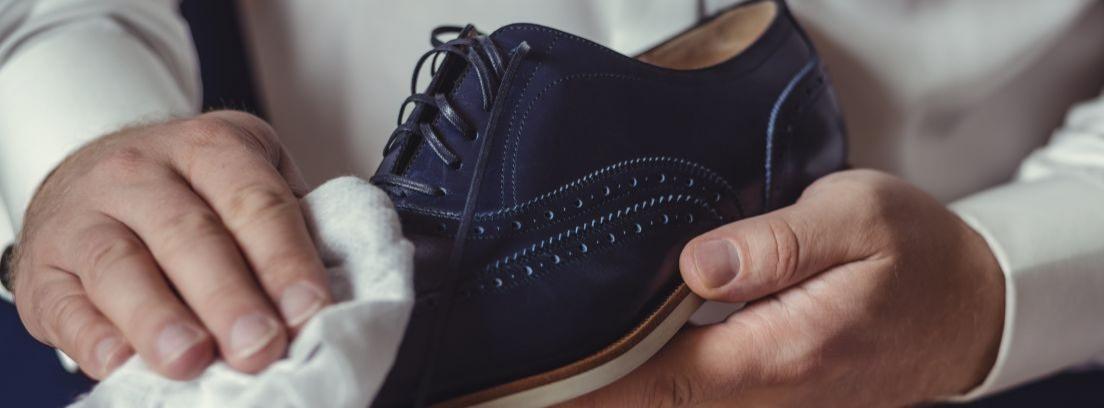 Manos limpiando con una gamuza blanca unos zapatos negros