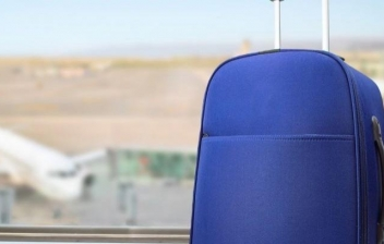 Dos maletas en un aeropuerto con un avión al fondo