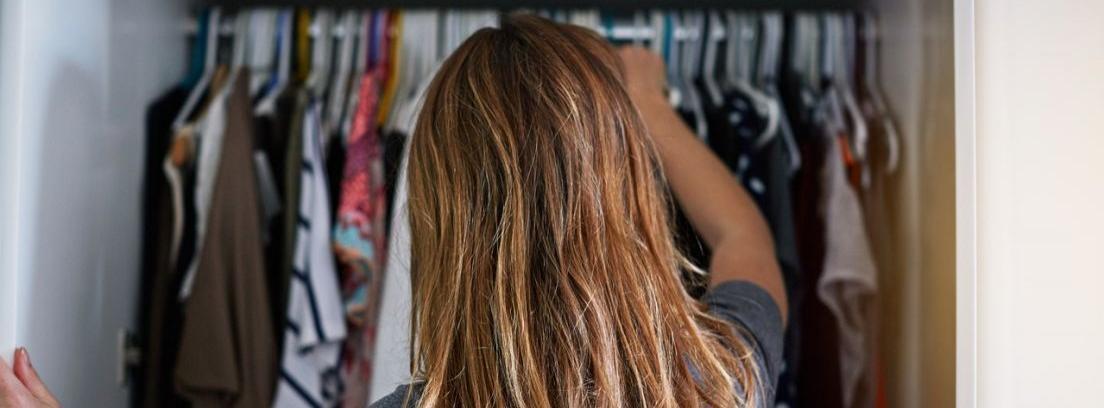 Mujer mira su armario preocupada